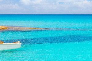 A boat floats on the crystal clear sea in Formentera, Spain.